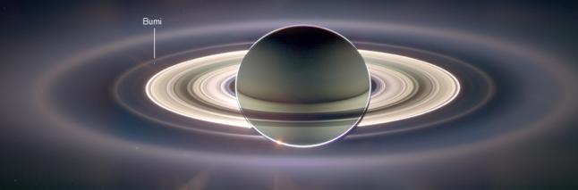 Bumi sebagai bintik kecil redup dibalik lapisan G cincin Saturnus saat diabadikan dari wahana Cassini pada 2006 silam tatkala Saturnus menggerhanai Matahari dilihat dari titik Cassini berada dalam orbitnya.  Sumber : NASA/JPL, 2006.