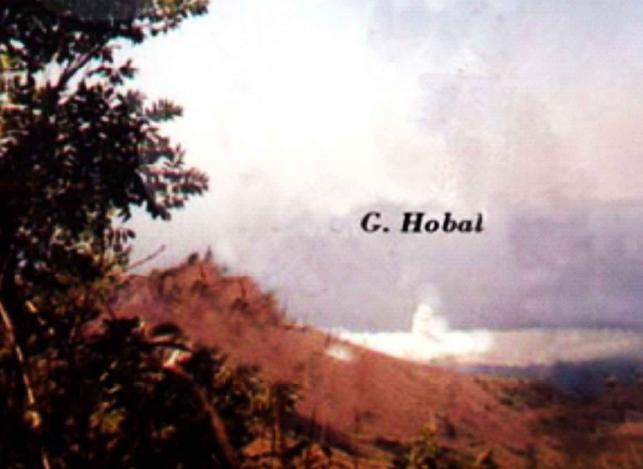 Semburan air dan uap panas dari lokasi Gunung Hobal saat Letusan 1999, diabadikan dari lereng Gunung Iliwerung. Nampak air laut di sekeliling pusat semburan berwarna lebih pucat ketimbang air laut pada umumnya. Sumber: Warta Geologi, 2010.