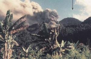 Gambar 4. Saat-saat awal kelahiran Gunung Anak Ranakah di dekat kota Ruteng (NTT) pada akhir Desember 1987. Nampak kolom debu vulkanik menyembur ke arah timur. Tanda panah menunjukkan lokasi bukit Ranakah dengan menara telekomunikasi Perumtel (kini PT Telkom) di puncaknya. Sumber: Rohi, 1988 dalam Wahyudin, 2012.