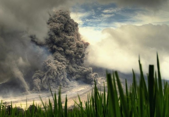 Gambar 2. Gunung Sinabung kala menghembuskan kolom letusan secara vertikal dan meluncurkan awan panas gugurannya pada 15 Januari 2014 lalu. Awan panas guguran nampak masih menyusuri jalur yang dilintasi awan-awan panas guguran sebelumnya. Diabadikan oleh Endro Lewa. Sumber: Lewa, 2014.