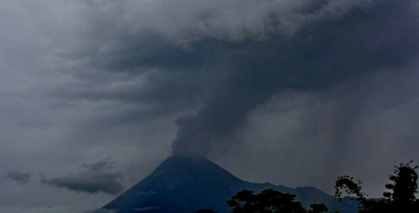 Gambar 1. Panorama puncak Gunung Merapi pada saat erupsi freatik 10 Maret 2014 lalu, diabadikan dari arah selatan oleh pak Bambang Mertani. Nampak kepulan asap menghembus ke atas untuk kemudian menyebar ke arah timur. Nampak pula hujan debu mulai mengguyur di lereng timur. Sumber: Bambang Mertani, 2014.
