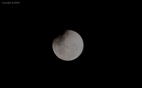 Gambar 2. Citra Bulan, juga pada tahap gerhana sebagian, diabadikan pada pukul 18:29 WIT pada ketinggian yang lebih besar (11,5 derajat). Nampak bagian cakram Bulan yang masih tergelapkan (sektor kiri atas) tinggal sedikit, mengingat kontak akhir umbra bakal berlangsung sebentar lagi (yakni pukul 18:33 WIT atau 4 menit lagi). Panduan arah: kanan = selatan, bawah = timur. Sumber: BMKG, 2014.
