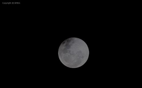 Gambar 3. Citra Bulan dalam tahap gerhana penumbra, diabadikan pada pukul 18:58 WIT (tinggi Bulan 18,5 derajat) menggunakan teleskop. Nampak terdapat bagian yang sedikit lebih gelap di sektor kiri atas sebagai penanda gerhana penumbra, yang hanya bisa disaksikan dengan alat bantu optik memadai. Panduan arah: kanan = selatan, bawah = timur. Sumber: BMKG, 2014.