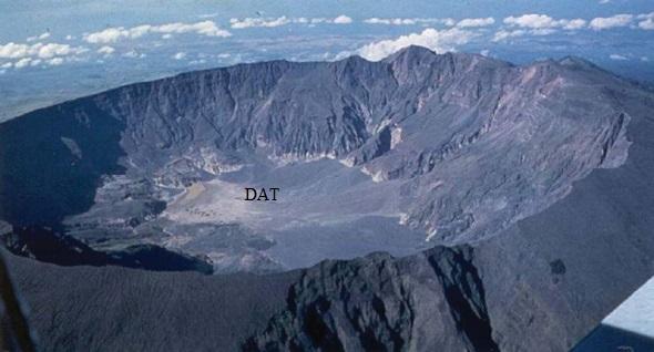 Gambar 1. Kawah raksasa (kaldera) yang menghiasi puncak Gunung Tambora saat ini, diabadikan dari udara dengan arah pandang ke timur laut. Kawah raksasa berdiameter 7 km sedalam 1.250 meter ini merupakan jejak paling kentara dari kedahsyatan Letusan Tambora 1815. Di dasar kawah raksasa ini tepatnya di sisi utaranya berdirilah si anak Tambora, yakni kerucut Doro Api Toi (DAT). Sumber: Pratomo, 2006.