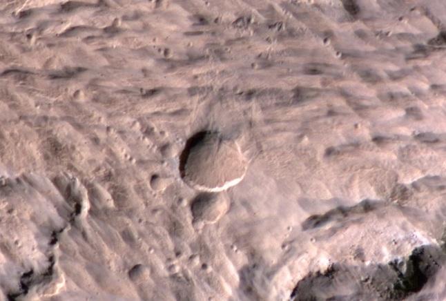 Gambar 1. Kawah bergaris tengah 48,5 meter di Mars yang terbentuk akibat hantaman meteoroid antara 27 hingga 28 Maret 2012, diabadikan oleh instrumen HiRISE wahana MRO. Panduan arah, atas = utara, kanan = timur. Di sebelah selatan kawah ini nampak kawah yang lebih kecil namun terbentuk pada saat yang sama. Terlihat pula adanya pencaran material produk tumbukan ke arah utara-timur laut. Sumber: NASA, 2014.