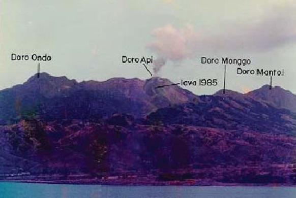 Gambar 4. Panorama titik-titik tertinggi pulau Sangeang yang sekaligus adalah puncak-puncak Gunung Sangeang Api, diabadikan dari daratan pulau Sumbawa. Kawah aktif masa kini terletak di puncak Doro Api, yang terlihat mengepulkan asap dan berhias leleran lava di sisi barat dayanya. Letusan besar Sangeang Api 2014 berpusat dari kawah ini dan kemungkinan menjebil kubah lava 1985 yang menutupi dasar kawah. Diabadikan oleh Heryadi Rahmat. Sumber: Rahmat, 1998 dalam Pratomo, 2006.