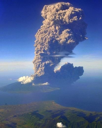 Gambar 1. Letusan Sangeang Api dalam menit-menit pertamanya diabadikan dari udara. Citra ini diambil oleh Sofyan Efendi, fotografer profesional yang kebetulan sedang menjadi penumpang salah satu penerbangan komersial dari Denpasar (Bali) ke Labuhan Bajo (Nusa Tenggara Barat). Letusan nampak bersumber dari tengah-tengah pulau Sangeang, lokasi dimana kawah Doro Api yang tersumbat kubah lava 1985 berada. Daratan di latar depan adalah bagian timur pulau Sumbawa. Sumber: Eefendi, 2014 dalam MailOnline, 2014.