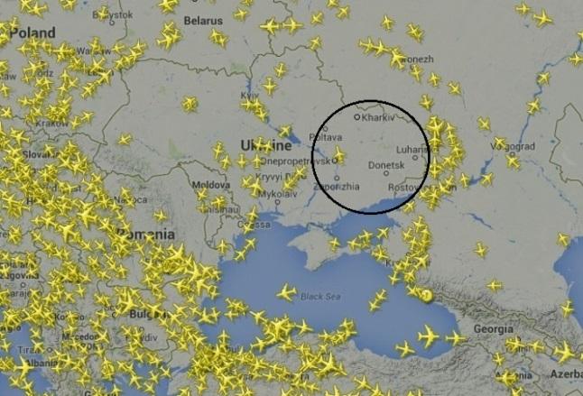 Gambar 4. Aktivitas lalu lintas udara di ruang udara Ukraina dan sekitarnya sehari pasca tragedi MH17. Nampak ruang udara Ukraina timur (dalam lingkaran hitam) yang sangat sepi, hanya dilintasi satu pesawat. Situasi ini sangat kontras dibanding ruang udara negara tetangga Ukraina seperti Rumania, Bulgaria dan Polandia yang demikian padat oleh lalu lintas penerbangan. Panduan arah: atas = utara, kanan = timur. Sumber: Flightradar24, 2014.