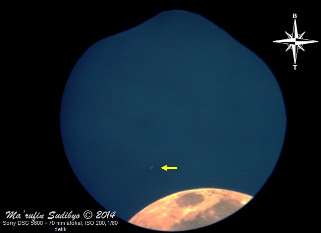 Gambar 1. Planet Saturnus (tanda panah kuning) sebagai segores garis cahaya redup di tengah langit yang masih terang benderang. Saturnus seakan mengambang di atas bagian Bulan yang hanya nampak sebagian saja di kawasan Mare Crisium dan sekitarnya. Diabadikan pada 4 Agustus 2014 dalam 10 menit sebelum terbenamnya Matahari dengan teknik afokal lewat eyepiece (okuler) 10 mm untuk kemudian diproses dengan GIMP 2. Sumber: Sudibyo, 2014.