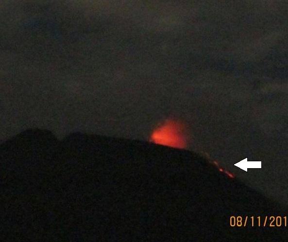 Gambar 1. Pancuran api Gunung Slamet, yang adalah lontaran material vulkanik berpijar mirip air mancur dari kawah aktif Slamet untuk kemudian berjatuhan kembali ke dalam/sekitar kawah sebagai ciri khas erupsi Strombolian. Pada status Siaga (Level III) kali ini, selain erupsi Strombolian juga telah terjadi leleran lava pijar ke arah barat-barat daya (tanda panah). Sumber: Hendrasto (Kepala PVMBG), 2014.