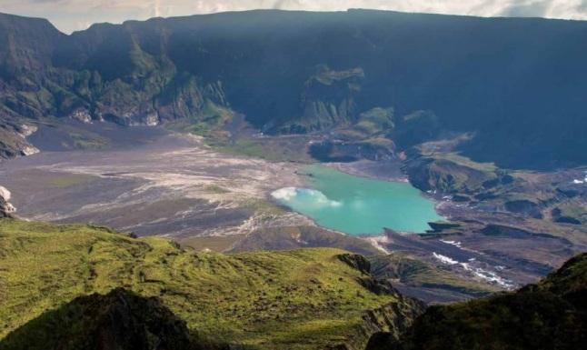 Gambar 5. Kaldera Gunung Tambora yang demikian luas dan dalam. Cekungan air berwarna kehijauan didasarnya adalah Danau Motilahalo. Kaldera ini terbentuk dalam Letusan Tambora 1815 yang dahsyat, hampir 2 abad silam. Kedahsyatannya memicu beragam dampak sosial-politis, termasuk Pertempuran Waterloo dan juga Perang Diponegoro. Sumber: Wahibur Rahman, dalam Geomagz vol. 4 no. 2 (Juni 2014).