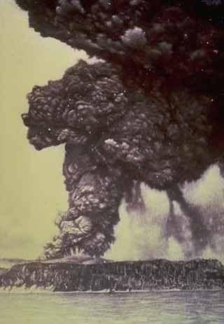 Gambar 1. Gunung Krakatau diabadikan pada Mei 188. Nampak debu vulkanik pekat mengepul dari puncak Perbuwatan, menandai mulai terjadinya erupsi magmatik di gunung berapi yang telah lama tidur ini. Dalam tiga bulan kemudian seluruh gunung ini menyemburkan material vulkanik dalam jumlah sangat besar yang ditembuskan hingga berpuluh kilometer ke atmosfer. Akibatnya hampir seluruh tubuh gunung hancur dan ambruk ke dasar laut menjadi kaldera, kecuali sebagian kecil lereng puncak Rakata. Sumber: USGS, 1982.