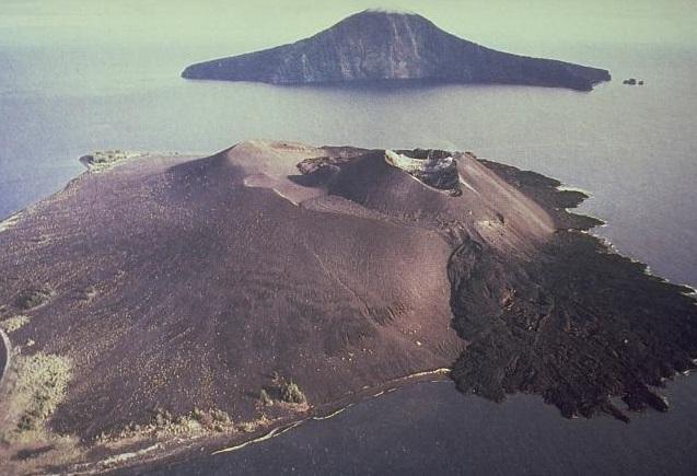 Gambar 1. Panorama Kepulauan Krakatau yang ikonik. Gundukan di latar depan adalah Gunung Anak Krakatau, dengan leleran lava produk letusan tahun 1975 yang telah membeku di bagian kanan bawah. Jauh di latar belakang terlihat pulau Rakata, yang adalah salah satu titik tertinggi dinding kaldera Letusan Krakatau 1883 yang mencuat di atas permukaan Laut. Kepulauan Krakatau mendunia lewat letusan dahsyatnya di tahun 1883. Namun jejak-jejak lapisan debu tebal yang tersingkap di berbagai pulau di kepulauan ini menunjukkan bahwa gunung berapi ini telah meletus dahsyat lebih dari sekali sepanjang sejarahnya. Sumber: Direktorat Vulkanologi (kini PVMBG), 1979.