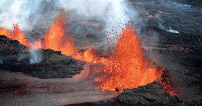 Gambar 1. Semburan magma basaltik hingga setinggi sekitar 100 meter menyeruak dari retakan di padang Holuhraun, sebagai perwujudan dari erupsi efusif Gunung Bardarbunga di Islandia. Letusan tidak menyemburkan debu vulkanik pekat ke langit, namun melelerkan lava panas membara yang mengukir permukaan tanah layaknya sungai api. Diabadikan oleh tim Reykjavik Helicopters pada awal September 2014. Sumber: Reykjavik Helicopters, 5 September 2014.