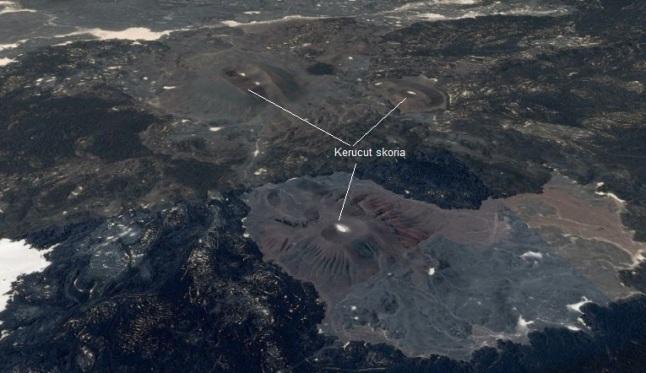 Gambar 6. Citra satelit Landsat dalam warna nyata untuk salah satu lokasi retakan yang menjadi sumber Letusan Madinah 1256. Nampak sejumlah kerucu skoria (cinder cone) yang dikelilingi bebatuan berwarna gelap (yang adalah endapan lava basaltik). Sumber: Google Earth, 2014.