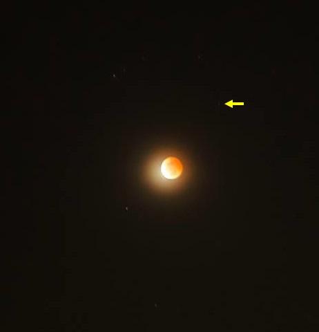 Gambar 4. Citra Bulan dan sekitarnya pada puncak Gerhana Bulan Total 8 Oktober 2014 diabadikan dari Jember (Jawa Timur) menggunakan panjang fokus 55 mm, ISO tinggi dan waktu penyinaran 15 detik. Citra telah diolah. Separuh wajah Bulan nampak berwarna kemerah-merahan (pertanda gerhana). Planet Uranus diperlihatkan dengan tanda panah. Sumber: Chandra Firmansyah, 2014.