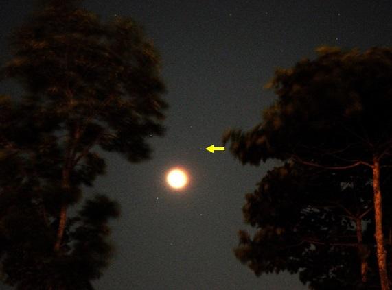 Gambar 3. Citra panoramik Bulan dan sekitarnya pada saat puncak Gerhana Bulan Total 8 Oktober 2014, diabadikan dari Jember (Jawa Timur) menggunakan panjang fokus 55 mm, ISO tinggi dan waktu penyinaran 15 detik. Bulan nampak sangat terang (pertanda tersaturasi). Planet Uranus diperlihatkan dengan tanda panah. Sumber: Chandra Firmansyah, 2014.