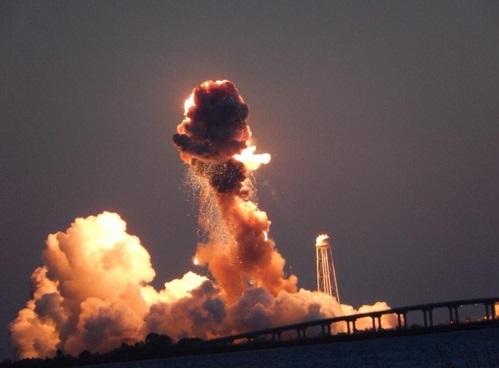 Gambar 2. Bola api ledakan (fireball) memijar terang bersama gumpalan asap pekat saat roket Antares meledak di detik-detik awal bencana, diabadikan di tengah-tengah kepanikan di pusat media yang berjarak hampir 2 kilometer dari landaspacu. Di latar belakang nampak menara air kompleks MARS, sementara di latar depan adalah jembatan gantung yang menghubungkan pulau Wallops dengan daratan Amerika Serikat. Sumber: Eduardo Encina, 2014.