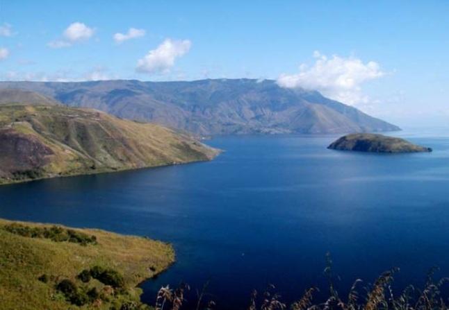 Gambar 1. Pemandangan sisi selatan Danau Toba yang permai. Nampak pulau Pardepur yang seakan mengapung di air danau. Pulau ini sejatinya merupakan salah satu kubah lava yang menyembul di paras danau, dari sejumlah kubah lava di sini yang terbentuk pasca letusan sangat dahsyat dalam kurun 74.000 tahun silam. Sumber: Sutawidjaja, 2008 dalam Warta Geologi, 2008.