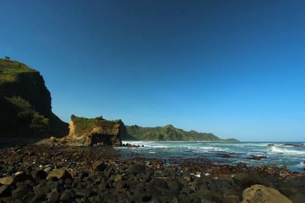 Gambar 7. Bongkah-bongkah potongan kekar kolom seukuran batubata di pantai Karangbata. Bongkah-bongkah tersebut nampaknya dihanyutkan dari lokasi singkapan kekar kolom di ujung tanjung Karangbata, yang menjadi pertanda pernah ada sebuah gunung berapi purba di kawasan ini.Sumber: Anonim, t.t.