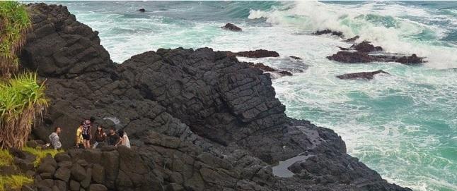 Gambar 6. Bebatuan beku mirip tiang-tiang batu yang saling bertumpuk di ujung tanjung Karangbata, pantai Menganti. Tiang-tiang batu tersebut merupakan balok yang adalah kekar kolom. Kekar kolom ini menjadi pertanda pernah ada sebuah gunung berapi purba di kawasan ini. Diabadikan oleh geolog Bambang Mertani. Sumber: Mertani, 2013.
