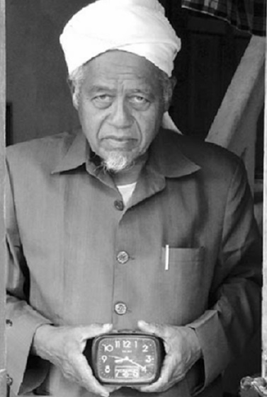Gambar 2. Imam Abu Abdul Rhaffar dari Lhoknga memegang sebuah jam manual yang berhenti pada pukul 09:20. Jam inilah salah satu saksi bisu kedahsyatan tsunami yang menggempur Lhoknga, dengan ketinggian gelombang hingga 50 meter dan menyerbu hanya dalam 20 menit pasca gempa dimulai. Sumber: Yulianto dkk, 2010.