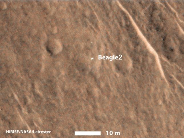 "Gambar 5. Wahana pendarat Beagle 2 dalam citra Mars Reconaissance Orbiter yang diperbesar. Nampak jelas Beagle 2 tetap utuh namun hanya dua ""daun"" yang mekar dari tubuhnya. Sementara tiga ""daun"" sisanya tak terlihat. Sumber: NASA, 2015."