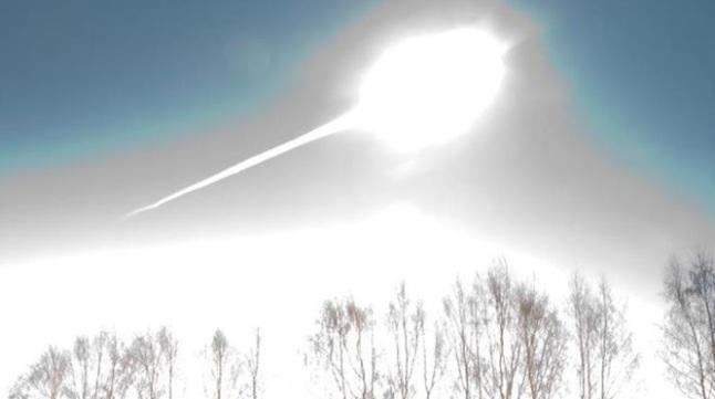 Gambar 1. Salah satu gambar ikonik Peristiwa Chelyabinsk 2013, yakni kala asteroid-tanpa-nama telah memasuki atmosfer Bumi dan mengalami kilatan cahaya pertama hingga lebih terang ketimbang Matahari. Kilatan cahaya ini terjadi saat asteroid, yang telah berubah menjadi boloid, sampai di ketinggian 29,7 kilometer dpl. Garis putih tebal lurus dibelakangnya adalah awan debu lurus (train) yang dibentuk boloid mulai dari ketinggian 97 kilometer dpl. Sumber: NASA APOD, 2013.