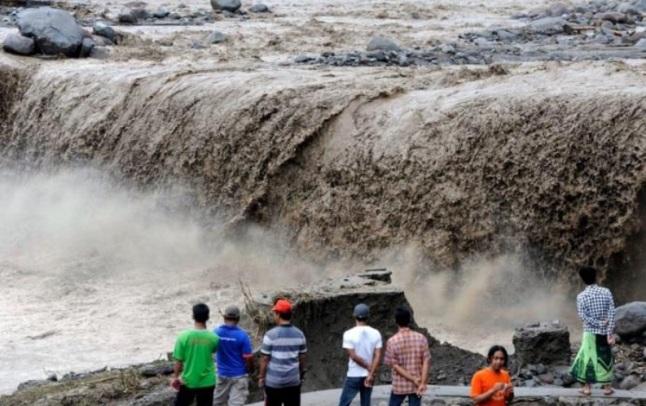 Gambar 8. Aliran lahar hujan Gunung Kelud pada 19 Februari 2014 TU di Pandansari (Malang). Lahar ini berasal dari material produk letusan yang bertumpukan di lereng dan kemudia dihanyutkan oleh air hujan. Selain lahar letusannya, salah satu dampak letusan Gunung Kelud terletak pada lahar hujannya. Terlebih hampir seluruh materi lahar hujan Gunung Kelud mengalir ke sungai Brantas. Aktivitas Gunung Kelud menjadi penyebab naik turunnya dasar sungai Brantas dan meluasya delta di muaranya. Hal ini tentu berdampak pada naik turunnya peradaban yang tumbuh dan berkembang di sepanjang lembah sungai ini. Sumber: Handoko, 2014 dalam Global Volcanism Program, 2014.