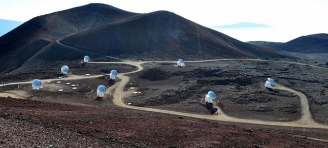 Gambar 3. Jajaran teleskop radio Smithsonian Submilimeter Array di kawasan puncak Gunung Mauna Kea, Hawaii (Amerika Serikat). Lewat jajaran teleskop radio semacam inilah dengan teknik VLBI, astronomi modern mengukur variasi rotasi Bumi setiap harinya dan waktu astronomik dengan bertumpu pada sinyal-sinyal gelombang elektromagnetik yang dipancarkan dari sumber kuat di luar galaksi Bima Sakti kita (quasar). Sumber: Darian, 2010.