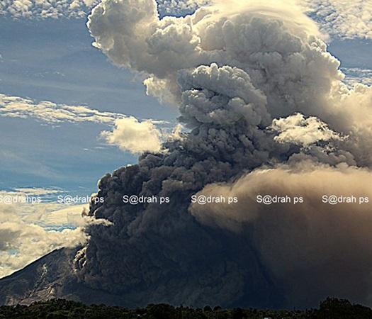 Gambar 2.  Salah satu dari 10 awan panas yang diluncurkan Gunung Sinabung pada 13 Juni 2015 TU. Ia berkibar ke arah selatan-tenggara hingga sejauh 3 kilometer dan membumbungkan debu vulkanik hingga setinggi 2 kilometer. Sumber: Sadrach Peranginangin, 2015.