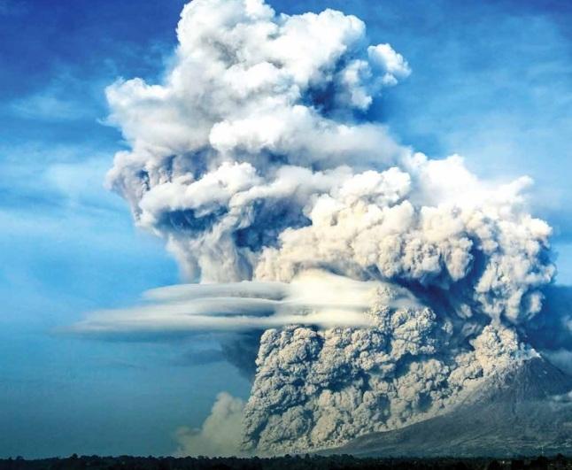 Gambar 1. Pemandangan menakjubkan, sekaligus mengerikan, saat Gunung Sinabung meluncurkan salah satu awan panas gugurannya ke arah lereng sektor tenggara dalam salah satu letusannya. Nampak jelas material awan panas yang berat dan bersuhu tinggi bergumpal-gumpal menuruni lereng. Tepat diatasnya debu vulkanik pekat mengepul ke atas membentuk awan debu vulkanik hingga ketinggian tertentu. Diabadikan oleh fotografer Hendi Syarifuddin pada 9 Februari 2015 TU dari arah kaki Sinabung sektor timur laut. Sumber: Syarifuddin, 2015 dalam Geomagz, Maret 2015.
