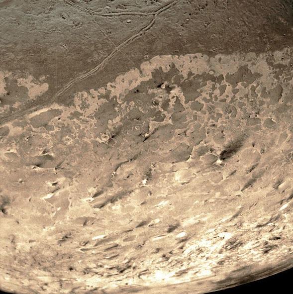 Gambar 7. Panorama kawasan di dekat kutub selatan Triton, diabadikan oleh wahana Voyager pada 1989 TU. Nampak goresan-goresan kehitaman dengan ketebalan beragam, menunjukkan jejak-jejak letusan gunung berapi di Triton sebagai ekspresi dari vulkanisme dinginnya yang unik. Sumber: NASA, 1989.