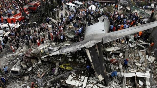 Gambar 1. Bangkai pesawat Hercules C-130B A-1310 TNI AU dilihat dari udara. Pesawat naas ini jatuh dalam kawasan yang relatif sempit dalam posisi terbalik di jalan Jamin Ginting, Medan (propinsi Sumatra Utara) pada Selasa 30 Juni 2015 TU. Ia hanya menyisakan bagian ekornya sebagai puing terbesar. Sumber: Reuters, 2015.