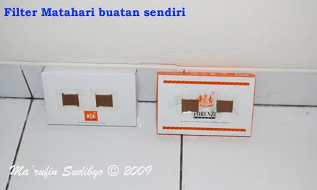 Gambar 8. Filter Matahari buatan sendiri, dibuat dengan menggunakan kotak kardus bekas wadah dompet yang dilubangi mirip kacamata lalu ditempeli negatif film yang telah dicuci. Sumber: Sudibyo, 2009.