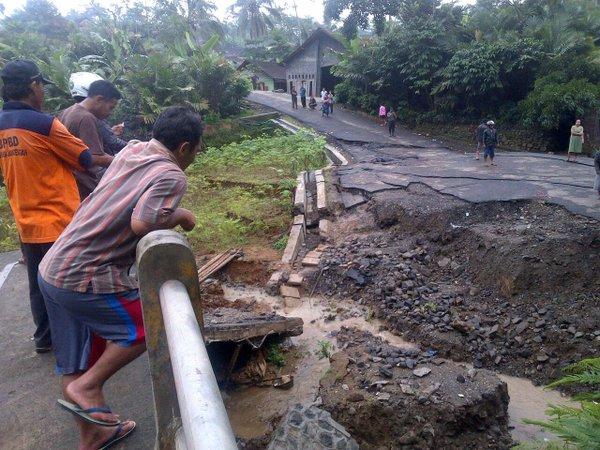 Gambar 1. Jembatan kecil yang menjadi saksi bisu bencana longsor Clapar pada hari-hari awal bencana itu. Jalan yang semula melintasi jembatan ini nampak sudah mulai terputus. Di hari-hari berikutnya penggal jalan raya ini kian jauh beringsut sekaligus tertimbuni lumpur oleh longsor rayapan yang terjadi. Sumber: Sutopo Purwo Nugroho/BNPB, 2016.