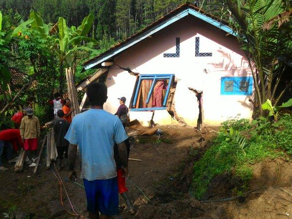 Gambar 2. Salah satu rumah permanen yang menjadi korban bencana longsor Clapar di hari-hari awal. Nampak ia rusak parah, telah retak separuh. Pada hari-hari berikutnya rumah ini kian rusak dan akhirnya runtuh sepenuhnya seiring gerakan tanah yang terus terjadi dalam longsor rayapan ini. Sumber: Sutopo Purwo Nugroho/BNPB, 2016.