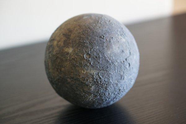 Gambar 3. Replika Merkurius berbentuk bola kecil yang parasnya telah dipahat sesuai paras Merkurius berdasarkan hasil pemetaan wantariksa MESSENGER. Merkurius adalah planet terkecil dalam tata surya kita, yang hanya sedikit lebih besar dari Bulan dan bahkan lebih kecil ketimbang Ganymede (satelit alamiah Jupiter) maupun Titan (satelit alamiah Saturnus). Dipahat oleh George Ioannidis di London (Inggris). Sumber: LittlePlanetFactory.com, 2016.