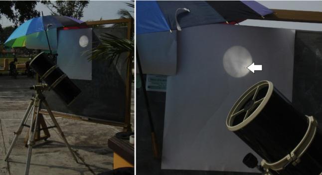 Gambar 6. Contoh penggunaan teknik proyeksi teleskopik dengan menggunakan teleskop reflektor (pemantul) Newtonian. Teleskop diarahkan ke Matahari, sementara citra yang dihasilkan langsung disorotkan ke layar proyeksi (dalam hal ini sehelai kertas putih di papan tulis). Fokus okulernya diatur demikian rupa agar citra di layar proyeksi tajam. Payung digunakan untuk melindungi layar proyeksi sehingga kontrasnya lebih besar. Teknik ini digunakan dalam observasi Transit Venus 2012 di Gombong, Kabupaten Kebumen (Jawa Tengah) oleh Forum Kajian Ilmu Falak Gombong. Panah menunjukkan kedudukan Venus. Sumber: Sudibyo, 2012.