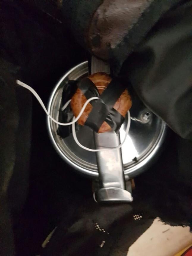 Gambar 1. Penampakan bom pressure cooker yang disita polisi dalam penggerebekan di Bekasi. Nampak panci tekan yang akan menjadi wadah. Nampak juga muatan primer berupa TATP seberat 3 kg (warna merah bata) yang telah dipasangi detonator (terlihat dari kabel yang menjulur). Sumber: Detikcom, 2016.