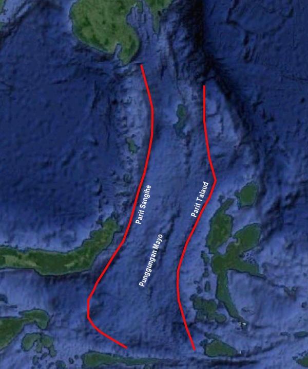 Gambar 1. Rona muka bumi kawasan Laut Maluku. Area di antara sepasang garis merah merupakan mikrolempeng Laut Maluku yang telah terdesak dan terbenam sepenuhnya oleh peristiwa tabrakan antar busur. Di sebelah barat (kiri) terdapat mikrolempeng Sangihe, bagian dari lempeng Eurasia yang mendesak ke arah timur. Sementara di sebelah timur terdapat mikrolempeng Halmahera yang mendesak ke arah barat seiring dorongan lempeng Laut Filipina. Sumber: Hamilton, 1979 dalam PusGen, 2017.